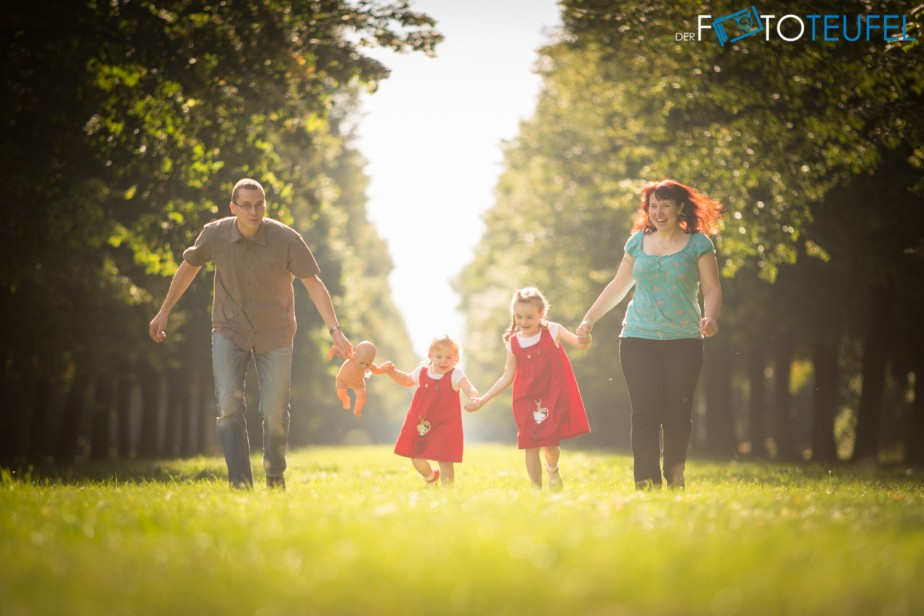 Cathl und Jan rennen mit ihren Kindern eine Allee im Großen Garten in Dresden entlang